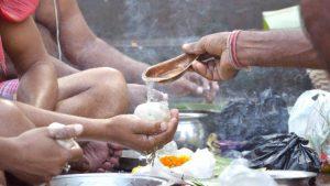 Men offering Tarpan during Pitru Paksha Rituals marking bhadra month