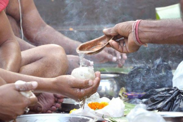 Men offering Tarpan during Pitru Paksha Rituals marking bhadra month